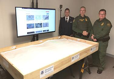 Figure 5 DHS S&T Senior Scientific and Technical Advisor Darren P. Wilson, U.S. Border Patrol Academy Chief Dan Harris, and U.S. Border Patrol Deputy Chief Scott Luck next to the transitioned Sandtable.